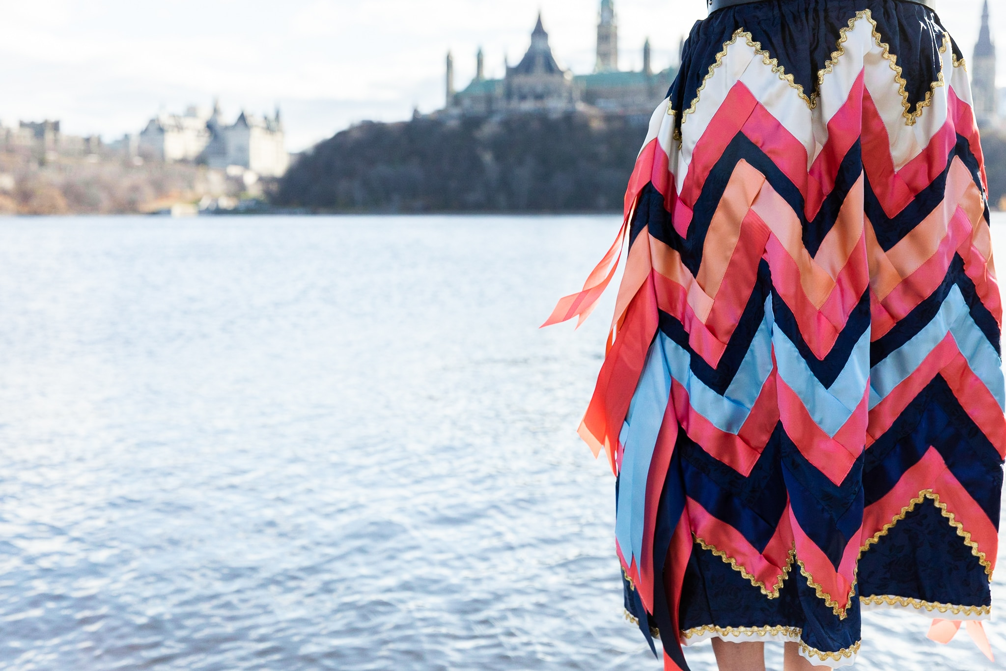 Autumn Peltier in her ribbon skirt on the Ottawa River, with the Canadian Parliment building in the background.
